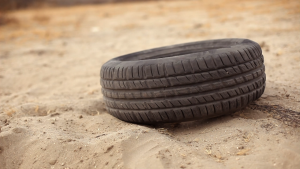 A rubber tire suddenly rises from the sand.